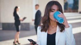 Portret van aantrekkelijke zakenvrouw die tijdens de koffiepauze Smartphone gebruikt Beauful Girl Manager staat buiten en stock videobeelden