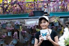 Portret van aardige jonge glimlachende vrouw met boek in bloemtuin royalty-vrije stock foto