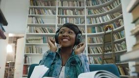 Portret van Afrikaanse aantrekkelijke jonge vrouw het luisteren muziek terwijl het rondhangen van de boeken stock video