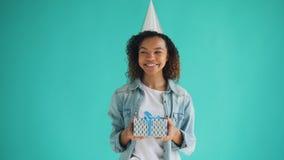 Portret van Afrikaanse Amerikaanse de gift van de feestvarkenholding doos en het glimlachen stock footage