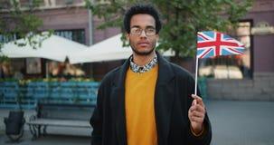 Portret van Afrikaanse Amerikaanse toerist Britse vlag houden die zich bevindt in de straat stock video