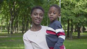 Portret van Afrikaanse Amerikaanse vrouw die haar zoon in haar wapens in het groene park dicht tegenhouden Leuke kind het bestede stock videobeelden