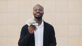 Portret van Afrikaanse Amerikaanse zakenman bevindende buitenkant dichtbij de bureaubouw die met hun geld pronken Zaken, mensen stock videobeelden