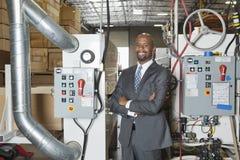 Portret van Afrikaanse Amerikaanse zakenman bevindende die wapens met machines op achtergrond worden gekruist stock foto