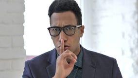 Portret van Afrikaanse zakenman gesturing stilte, vinger op lippen stock videobeelden