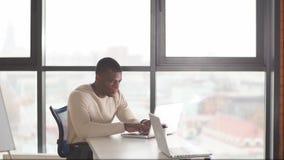 Portret van Afrikaanse zakenmanzitting bij bureau die computer met behulp van stock videobeelden
