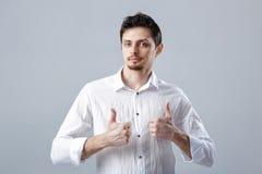 Portret van ahandsom die de Donkerbruine mens in overhemd glimlachen die duimen tonen Royalty-vrije Stock Foto's