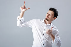 Portret van ahandsom die de Donkerbruine mens in overhemd glimlachen die duimen tonen Stock Fotografie