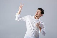 Portret van ahandsom die de Donkerbruine mens in overhemd glimlachen die duimen tonen Royalty-vrije Stock Foto