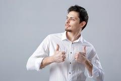 Portret van ahandsom die de Donkerbruine mens in overhemd glimlachen die duimen tonen Stock Foto