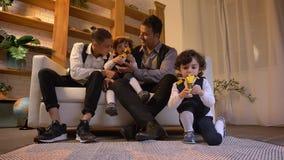 Portret van Arabische vaderzitting op bank met zijn tweelingzonen en tiener en het spelen met speelgoed in woonkamer stock video