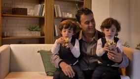 Portret van Arabische vaderzitting op middelbare leeftijd op bank met zijn tweelingzonen die met speelgoed-robots in woonkamer sp stock video