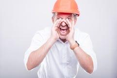 Portret van architect die bouwvakker luid gillen dragen uit stock afbeelding