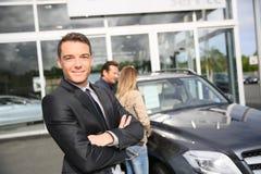 Portret van autoverkoper met cliënten in de rug royalty-vrije stock foto's