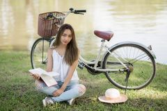 Portret van Aziatisch meisje gelezen boek bij park stock foto's