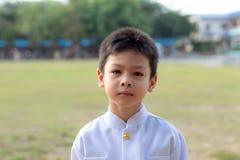 Portret van Aziatische jongen die een wit overhemd in het gras dragen royalty-vrije stock fotografie