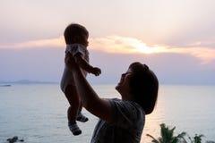 Portret van Aziatische moeder en baby op het strand Stock Afbeelding