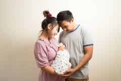 Portret van Aziatische ouders en zes van het babymaanden oud meisje thuis Royalty-vrije Stock Foto's