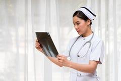 Portret van Aziatische Verpleegsterscontrole X Ray Film stock foto