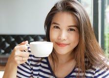 Portret van Aziatische vrouw die en kop o glimlachen houden stock fotografie