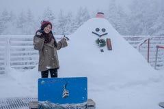 Portret van Aziatische vrouw op rode wolhoed met sneeuwman stock afbeeldingen