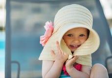 Portret van baby het verbergen in grote hoed Stock Afbeelding