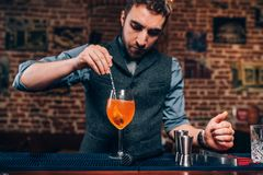 Portret van barman die cocktail voorbereiden, die alcoholische drank in nachtclub verfrissen Stock Foto