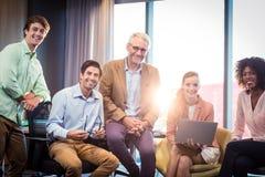 Portret van bedrijfsmensen die terwijl het hebben van bespreking over tablet glimlachen Royalty-vrije Stock Foto