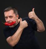 Bejaarde met Spaanse peper in zijn mond Royalty-vrije Stock Fotografie