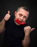Bejaarde met Spaanse peper in zijn mond Stock Foto