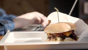 Portret van bezige jonge bedrijfsmensenzitting met glas van drank en hamburger in het binnenland van het snel voedselrestaurant stock video