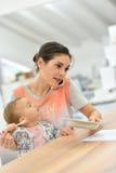 Portret van bezige moeder met baby en het werken royalty-vrije stock fotografie