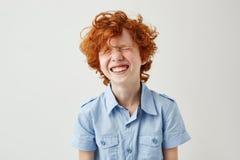 Portret van blij weinig jongen met gemberhaar en sproeten lachen uit luid met gesloten ogen in klaslokaal tijdens onderbreking royalty-vrije stock foto's