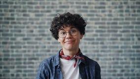 Portret van blije jonge vrouw die grappige gezichten op baksteenachtergrond maken stock videobeelden