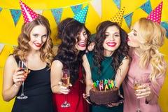 Portret van blije vrienden die en camera verjaardagspartij roosteren bekijken Glimlachende meisjes met glazen champagne Stock Fotografie