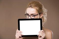 Portret van blonde in glazen met een tablet in handen stock afbeelding