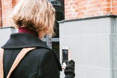Portret van Blonde kroezig meisje die beelden van Vensters op mobiel apparaat nemen stock foto