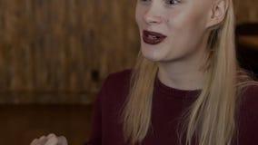 Portret van blonde vrouw, die aan haar frends spreekt stock video