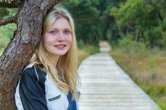 Portret van blondemeisje met boomstam en weg in aard Stock Fotografie