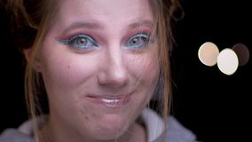 Portret van blondemeisje met kleurrijke samenstelling die haar haar van gezicht met grappige frustratie op vage lichten blazen stock videobeelden