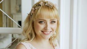 Portret van blondemeisje met tiara die zich door het venster bevinden stock videobeelden