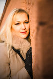Portret van blondemeisje in warme laag over een bakstenen muur Stock Foto's