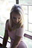 Portret van blondevrouw het stellen voor venster Stock Foto