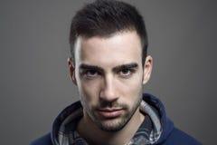 Portret van boos jong gebaard mannetje die hoodie het staren bij camera dragen royalty-vrije stock fotografie