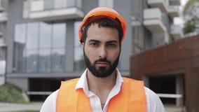 Portret van bouwvakker op bouwterrein die de camera bekijken De bouwer bevindt zich tegen de achtergrond van a stock videobeelden