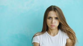 Portret van boze jonge vrouw die camera zenuwachtig op blauwe achtergrond onderzoeken Stock Afbeelding