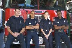 Portret van brandbestrijders die zich door een brandmotor bevinden stock afbeelding