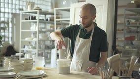 Portret van ceramist, die email op de oppervlakte van mok in zijn heldere studio toepast stock video