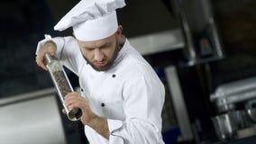 Portret van chef-kok het koken bij keuken Het peppering voedsel van de close-upchef-kok in langzame motie stock footage