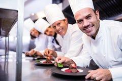 Portret van chef-koksteam het eindigen dessertplaten Royalty-vrije Stock Foto